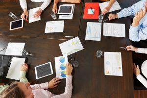 Tisch im Büro mit Händen und vielen Dokumenten von oben